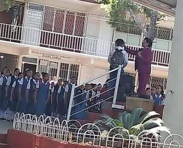 Micaela Zapata trasquilando al estudiante.