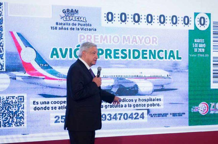 AMLO presentando el boleto de la rifa del avión presidencial.